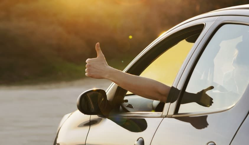 person giving thumbs up from car